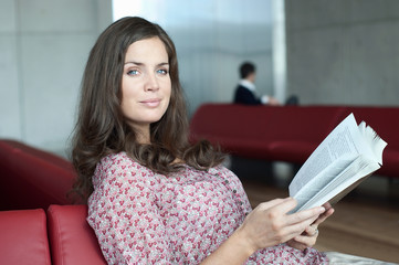 Woman reading in airport lounge
