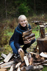 Woman gathering firewood in forest