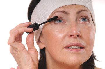 Closeup portrait of mature woman applying mascara on eyelashes
