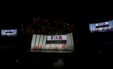 Women hold up national flags during the opening ceremony of the 66th FIFA Congress in Mexico City