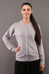 Young hipster girl wearing blank grey cotton zip up sweatshirt with copy space for your design or logo, mock-up of ltemplate womens hoodie, grey wall in the background