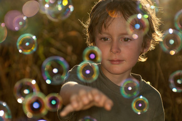 Boy playing with bubbles outdoors