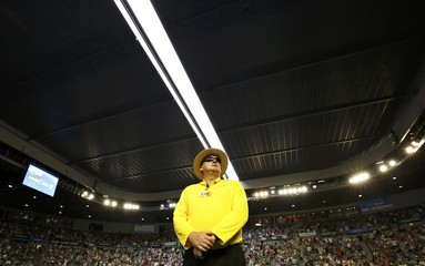 A security guard stands on court as the roof is closed at the Rod Laver Arena during the quarter-final match between Britain's Murray and Spain's Ferrer at the Australian Open tennis tournament at Melbourne Park