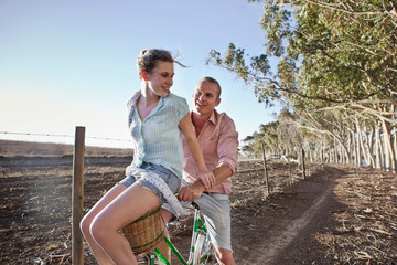 Young woman sitting on front of boyfriend's bicycle