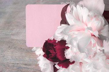 A bouquet of peony flowers with a note in pink tones. Wooden table. Romantic mood. Toned in pink photo. Top view