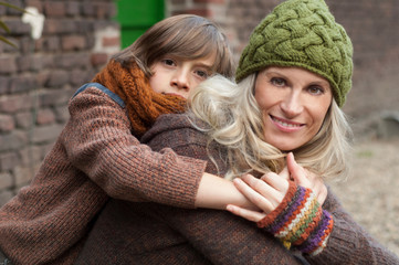 Boy embracing mother outdoors, smiling