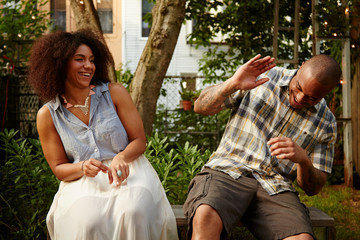 Mid adult man laughing with woman at garden party