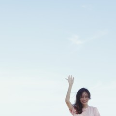 Portrait Of Young Woman With Arm Raised Against Clear Sky