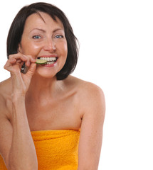 Happy senior woman in spa towel eating piece of cucumber