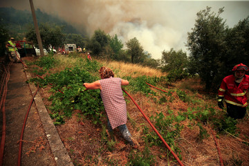A woman helps firefighters as they work to put out a forest fire in the village of Sandinha