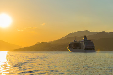 A large liner sails in the rays of the sunset along the Boka-Kotorska Bay. Montenegro.