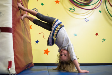 Young girl doing handstand in soft play area