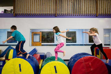 Children playing in soft play area, running across cylindrical shapes