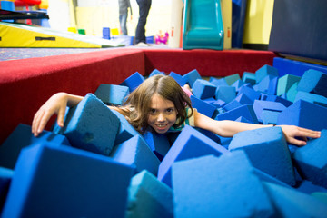 Young girl playing in foam cube pit