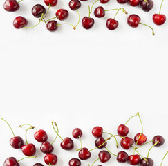 Cherries at border of image with copy space for text. Top view. Ripe cherry on a white background. Background berries.