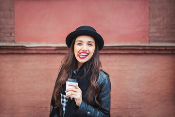 Young stylish woman in a city street drinking coffee and having fun