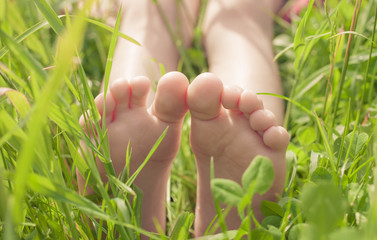 Kid bare feet in green grass. Lifestyle concept