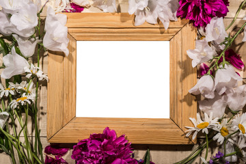 Wooden baguette with flowers lies on a wooden table,frame for inserting photos