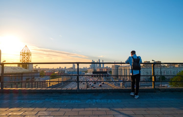 """Photographer taking picture above Moscow cityscape with Third Transport Ring road and modern architecture of """"Moscow City"""" Business Center, Russia. Phrase on asphalt """"I love you to"""" in Russian"""
