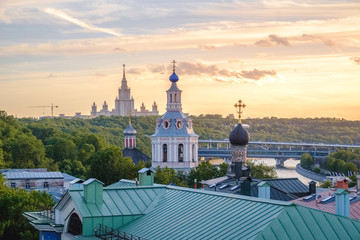 The buildings of Moscow city center at sunset time with State University silhouette, some classical old church and colorful roofs. Golden sunset lights above Moscow, outdoor summer evening in Russia.