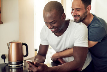 Black and white smiling gay couple with smartphone in kitchen