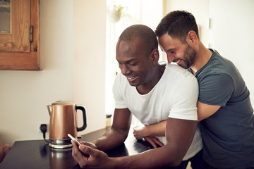 Multiethnic soft gay couple browsing smartphone in kitchen