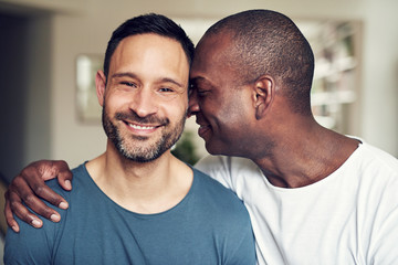 Romantic adult gay couple embracing and smiling together