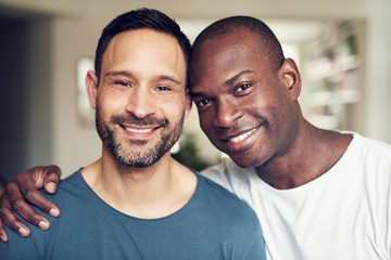 Smiling adult multiethnic gay couple looking at camera