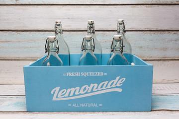 Botellas de cristal en caja de madera azul.