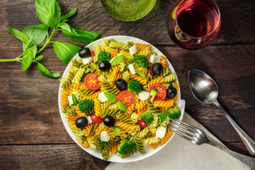 Pasta salad with basil and wine on rustic texture