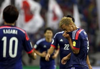 Japan's Honda reacts after scoring a goal against Cambodia as teammates Kagawa and Yoshida walk to celebrate during their 2018 World Cup qualifying soccer match at Saitama Stadium in Saitama