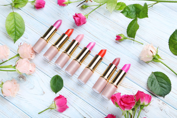Colorful lipsticks on white wooden table