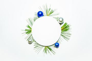 X-mas background with christmas balls and green pine leaves. Round copy space for text
