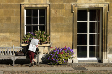 Woman reading newspaper on a bench in Cambridge, England