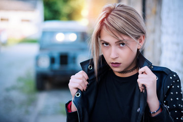 Portrait of a young punk rock fashion girl wearing black leather jacket with studs in urban warehouse street environment
