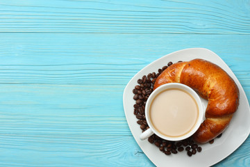 Coffee background. Cup of coffee with croissant and coffee beans on blue wooden background. Top view with copy space.
