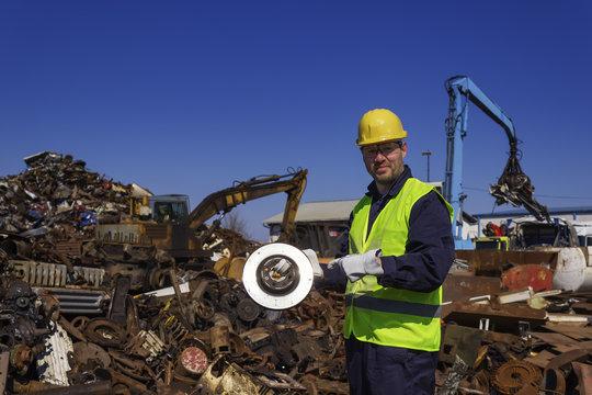 Inspector hold old car rotor on junkyard
