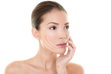 Face lift treatment anti aging skincare beauty woman concept. Skin care Asian model touching face with lifting arrows lines facelift design. Portrait in studio isolated on white background.