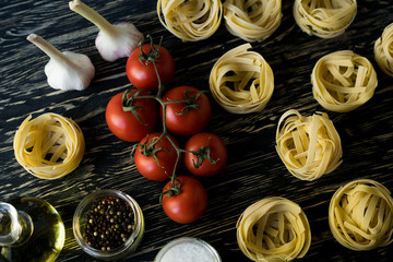 Pasta ingridients and spice on wooden surface.