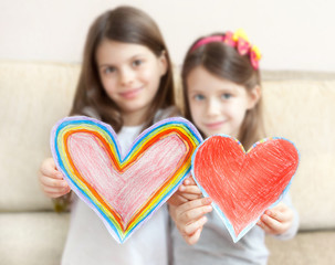 Two little girls (5 - 7 years old ) give painted hearts. Father's Day (mothers Day). Girls shooted soft focus. Hearts shooted sharp focus focus. Light background.