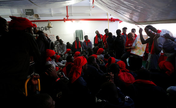 """A """"Save the Children"""" member shows Italy's map to migrants has they approach the south Italy coast on Vos Hestia ship after being rescued Mediterranean sea off Libya coast"""