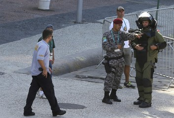 An agent of the bomb squad in protective clothing stands in the area near the finishing line of the men's cycling road race at the 2016 Rio Olympics after they made a controlled explosion, in Copacabana