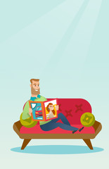 Man reading a magazine on the couch.