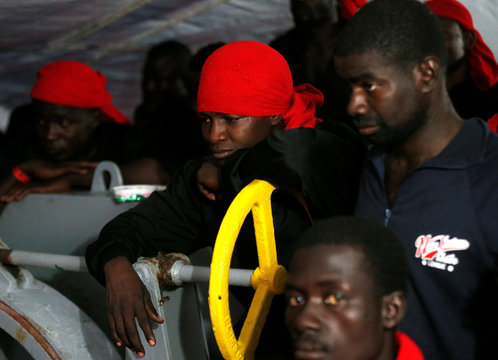 """Migrants listen as a """"Save the Children"""" member shows Italy's map as they approach the south Italy coast on the Vos Hestia ship after being rescued in the Mediterranean sea off the Libya coast"""