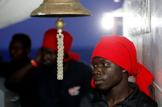 """A migrant listens as a """"Save the Children"""" member shows Italy's map as they approach the south Italy coast on the Vos Hestia ship after being rescued in the Mediterranean sea off the Libya coast"""