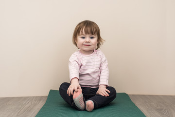 adorable smiling baby girl with big blue eyes sitting on the yoga mat and looking into the camera