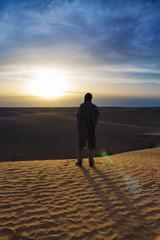 силуэт мужчины  в песчаной пустыне при закате солнца