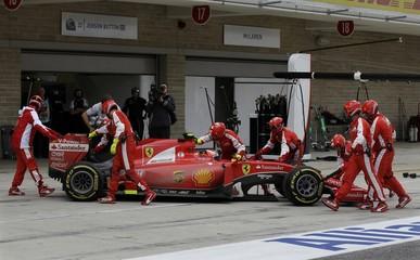 Mechanics push Ferrari's Kimi Raikkonen, of Finland, back into the team garage during the Formula One U.S. Grand Prix auto race at the Circuit of the Americas in Austin
