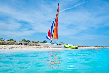 Wall Mural - The beautiful beach of Varadero in Cuba with a colorful sailboat