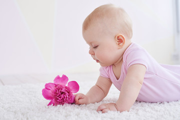Cute baby looking at a flower